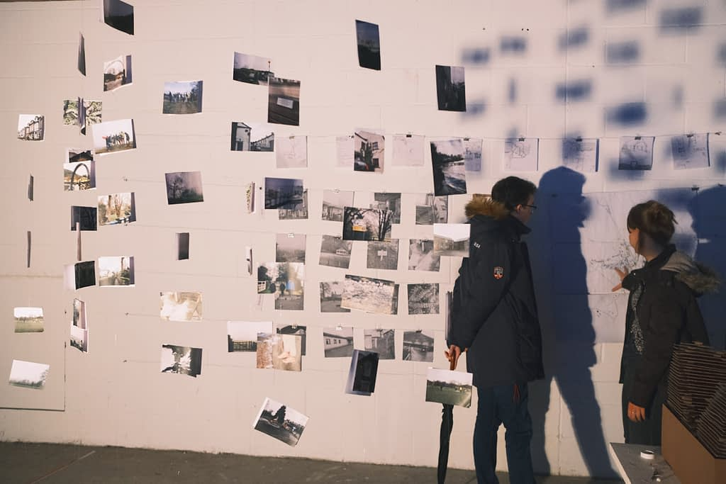 The exhibition visitors look at drawings and photos hung on a fishing wire.